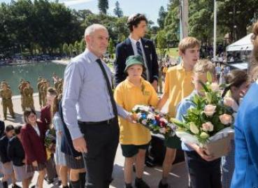 A teacher assists his students to lay a floral wreath on the Memorial's northern stairs
